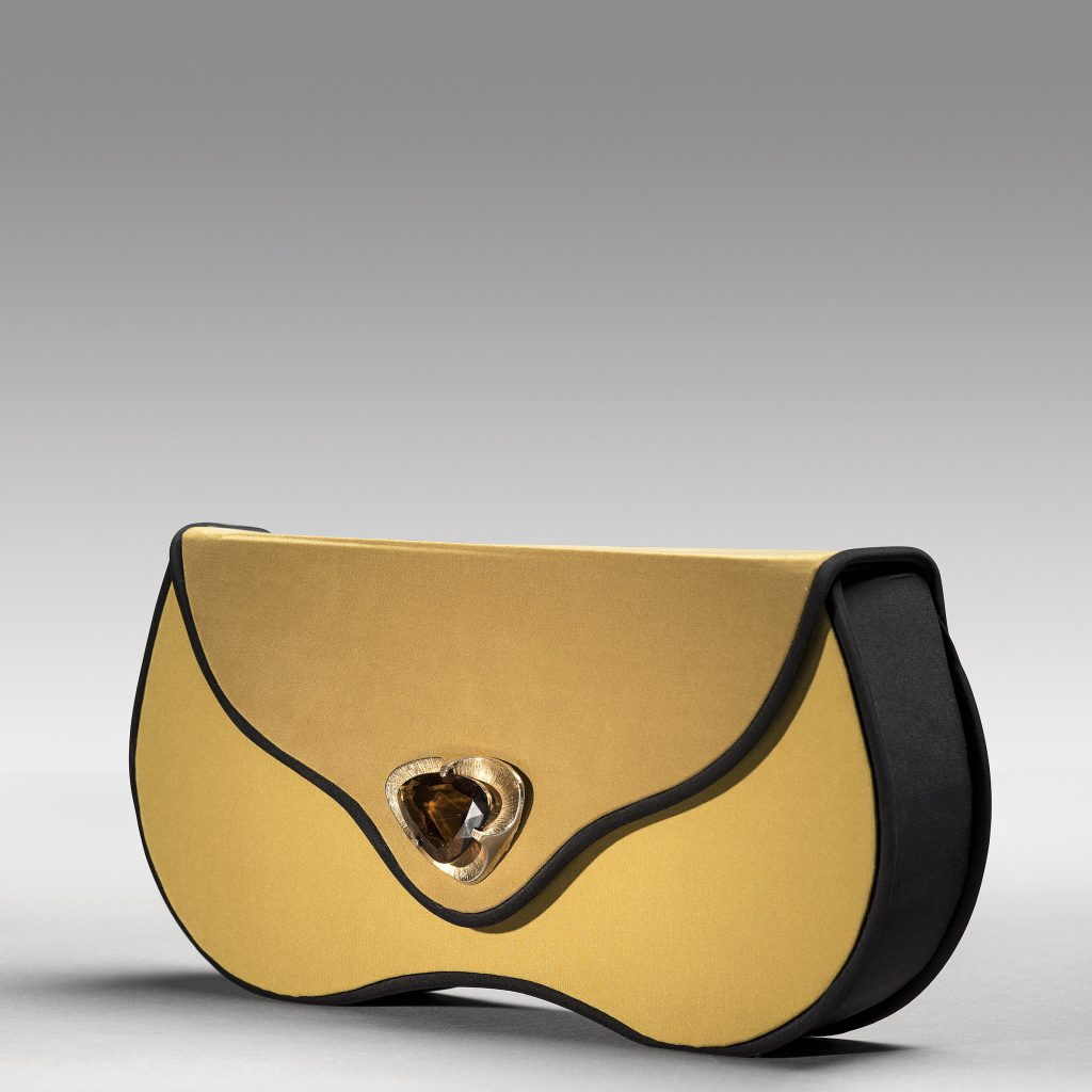 Voluptuously-shaped clutch embellished with large vintage brooch.